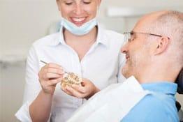 Zahnärztin mit Patient und Zahnersatz